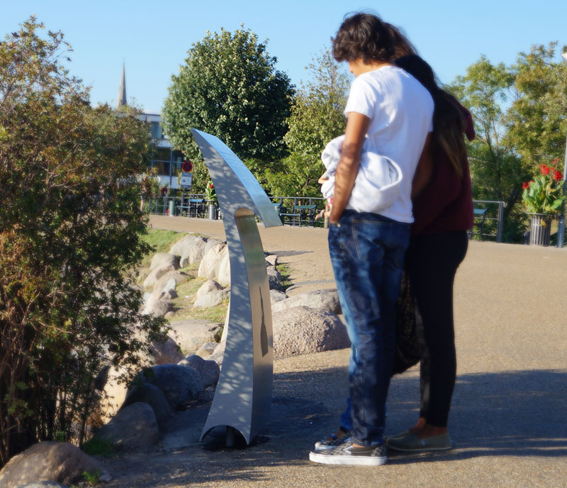 Turister kigger på havfrue skilt